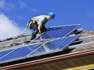 A man installing solar panels onto a roof